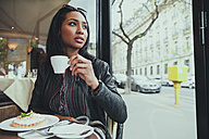 Portrait of young woman sitting in a cafe drinking coffee - ZEDF000086