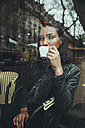 Portrait of young woman sitting behind windowpane of a cafe drinking coffee - ZEDF000089