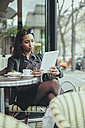 Portrait of young woman sitting in a cafe using digital tablet - ZEDF000092