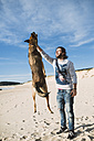 Man playing with his mongrel on the beach - RAEF001142