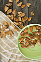Almonds, green plate, kitchen towel on wood, cracked - JPF000136