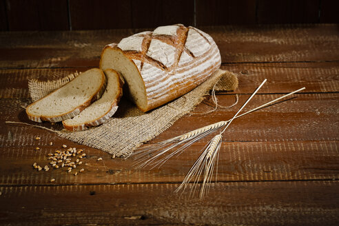 Brown bread on jute and baking paper, slices, spikes - MAEF011458