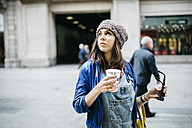 Spain, Barcelona, young woman with a coffee in the city - JRFF000615