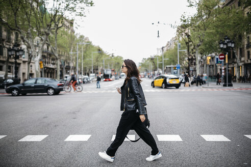 Spain, Barcelona, young woman in the city crossing street - JRFF000624
