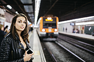 Young woman on train station awaiting train coming in - JRFF000627