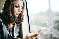 Young woman on train looking on cell phone - JRFF000630
