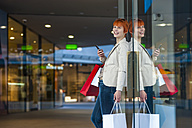 Happy young woman with cell phone and shopping bags - DIGF000402