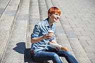Happy young woman sitting on stairs with coffee to go - DIGF000444