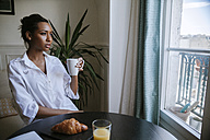 Young woman sitting at breakfast with cup of coffee looking through window - ZEDF000096