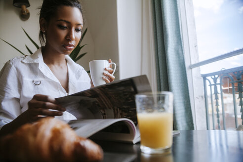 Portrait of young woman reading magazine at breakfast table - ZEDF000099