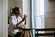 Young woman sitting at breakfast with cup of coffee looking through window - ZEDF000102