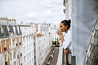 France, Paris, young woman with cup of coffee leaning out of window - ZEDF000108
