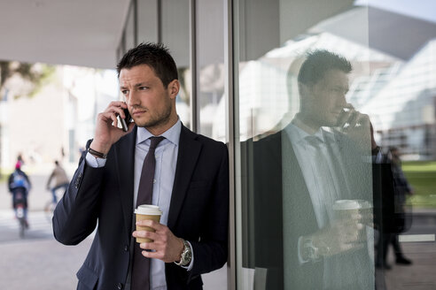 Businessman outdoors with cell phone and coffee to go - MAUF000508