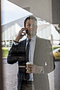 Businessman outdoors with cell phone and coffee to go - MAUF000511