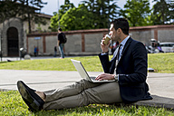 Businessman sitting on meadow with laptop and coffee to go - MAUF000523