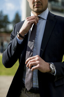 Businessman outdoors adjusting tie - MAUF000526