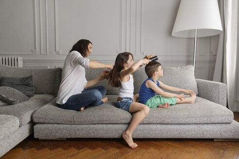 Mother and her children sitting in a row on the couch combing their hair with hairbrushes - LITF000274