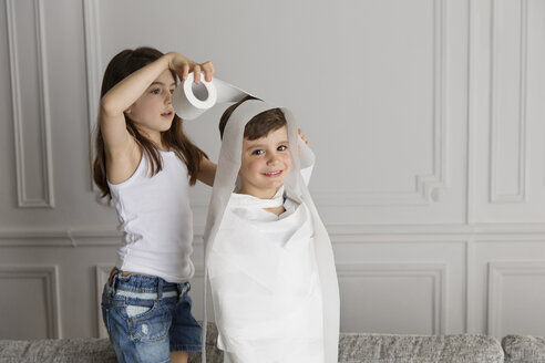 Girl wrapping toilet paper around her little brother at home - LITF000277