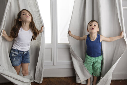 Siblings playing peek-a-boo with curtains - LITF000280