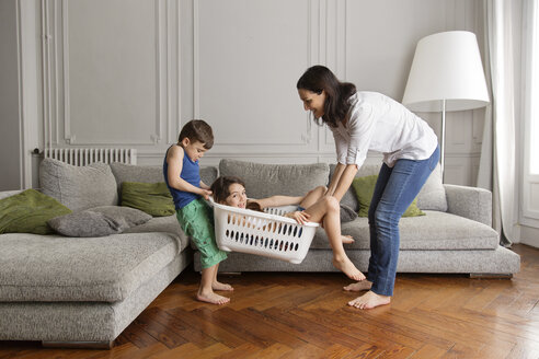 Mother and little brother carrying big sister in the laundry basket - LITF000286