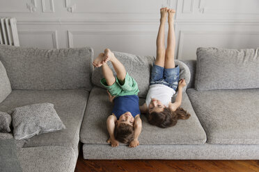 Two little children playing on the couch upside down with their legs in the air - LITF000289