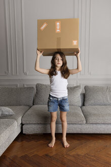Portrait of little girl holding a cardboard box over her head at home - LITF000295