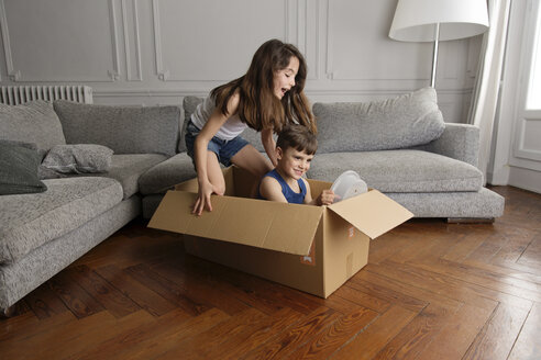 Girl and little brother playing together in a cardboard box at home - LITF000298