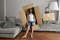 Girl and little brother playing with cardboard boxes at home - LITF000301