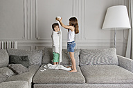 Girl wrapping toilet paper around her little brother at home - LITF000304