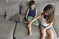 Little girl putting a band-aid on her brother's leg - LITF000307