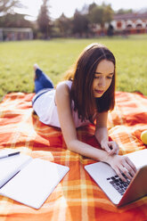 Student at the park learning at a laptop - GIOF000947