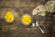 Two glasses of overnight oats with diced mango on wood - LVF004852