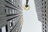 Germany, Berlin, lighted street lamp between two skyscrapers seen from below - ZMF000467