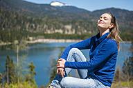 Germany, Bavaria, woman relaxing at lake Barmsee - DIGF000468