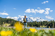 Germany, Bavaria, woman walking at lake Barmsee - DIGF000480