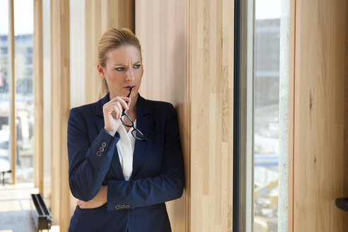 Businesswoman leaning against wall thinking - CHAF001679