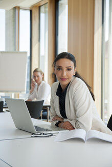Portrait of confident businesswoman in office with laptop - CHAF001688