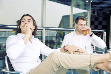 Two young men smoking and drinking beer on cruise ship - SEF000903