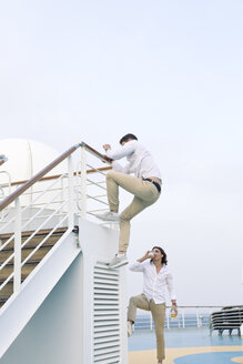 Two young men messing about on cruise ship, climbing on railing - SEF000906