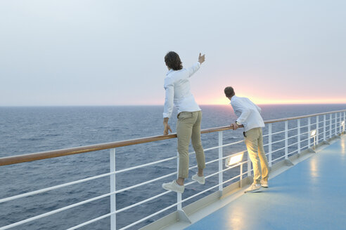 Young men standing on deck of ship, watching sunset - SEF000912