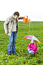 Father with watering can and daughter with umbrella on meadow - MAEF011615