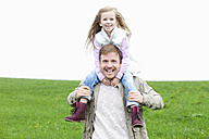Happy father carrying daughter on shoulders on meadow - MAEF011623