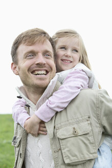 Happy father carrying daughter piggyback outdoors - MAEF011629