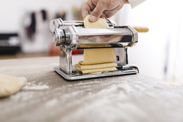 Chef rolling dough with pasta machine - JRFF000655