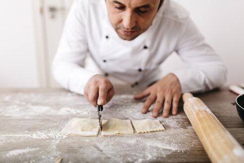 Chef cutting fresh ravioli - JRFF000658