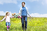 Happy father and daughter walking with doll in meadow - MAEF011647
