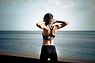 Back view of woman doing workout in front of the sea - SIPF000441
