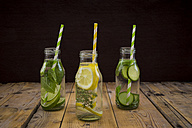 Three glass bottles of table water flavored with different fruits and herbs - LVF004857
