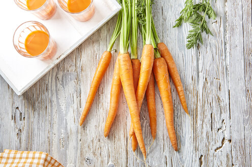 Carrots and three glasses of carrot juice on wood - KSWF001762