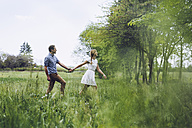 Couple in love holding hands while walking on a meadow - GIOF000986